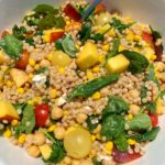 The best summertime couscous filled with fresh ingredients like cherry tomatoes, peaches, corn, leafy greens and more. This healthy and easy BBQ side dish has become a family and friend favorite and it is an easy vegetarian dish to make!