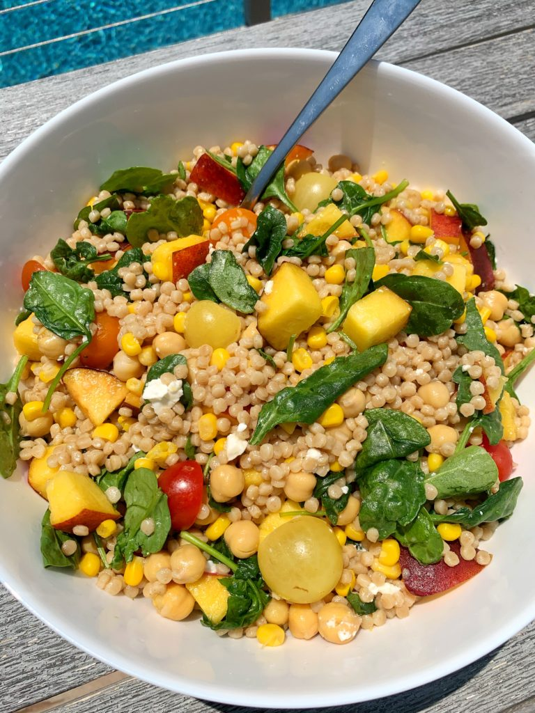 The best summertime couscous salad filled with fresh ingredients like cherry tomatoes, peaches, corn, leafy greens and more. This healthy and easy BBQ side dish has become a family and friend favorite and it is an easy vegetarian dish to make!