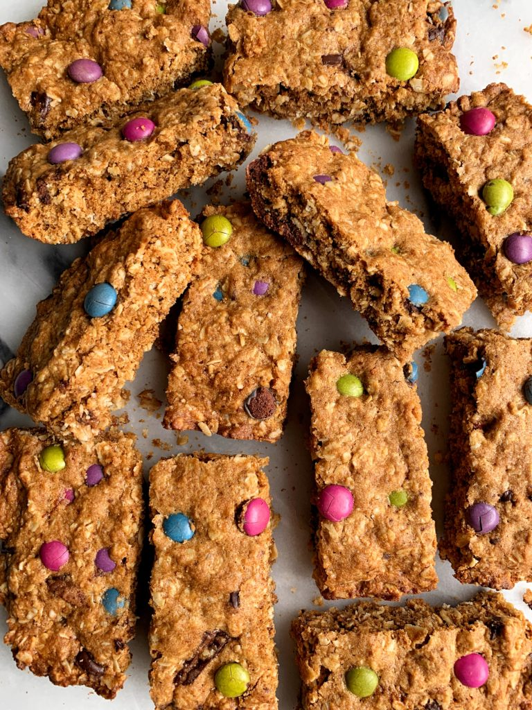 Healthier Gluten-free Monster Oatmeal Cookie Bars that taste like an oatmeal cookie dream! Filled with organic m&m candies and these oatmeal cookie bars are dairy-free, gluten-free and so delicious.