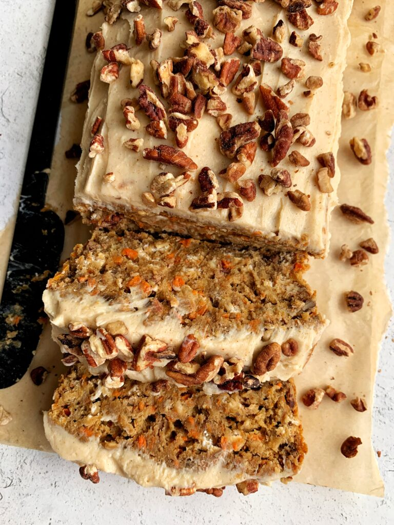 Vegan Carrot Cake Banana Bread with a dreamy and delicious cream cheese frosting! The ultimate gluten-free carrot cake banana bread made with all healthier ingredients and topped with cinnamon cream cheese frosting.