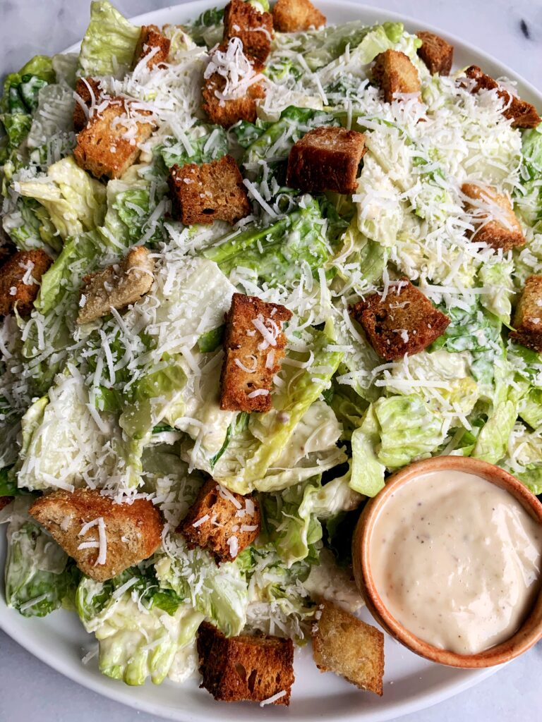 The Best Healthy Classic Caesar Salad with homemade caesar dressing, baked sourdough croutons on top of crunchy romaine with a sprinkle of fresh parmesan cheese.