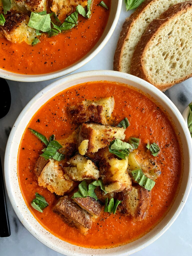 "This healthier Vegan Creamy Tomato Soup with Grilled Cheese Croutons is the ultimate comfort food recipe! The dairy-free soup is made with 5 ingredients and topped with delicious grilled cheese made into ""croutons""."