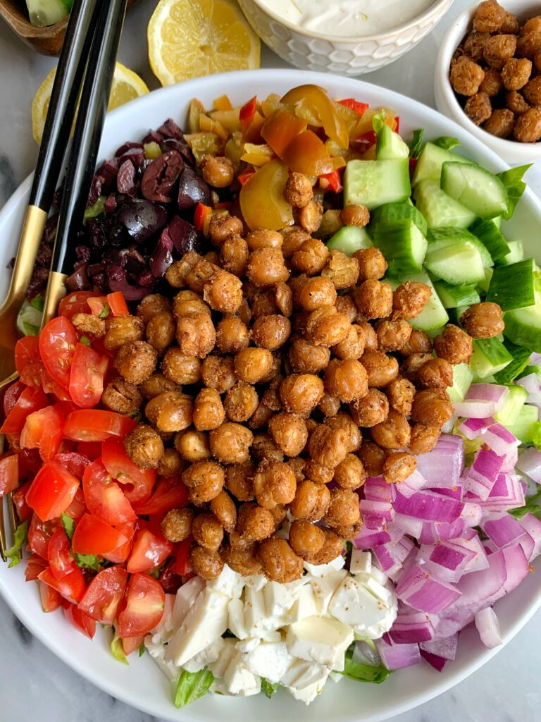 This Vegetarian Greek Salad with Tahini Yogurt Dressing is filled with all your Greeks salad favorites plus it's topped with crispy chickpeas and tossed in a delicious tahini yogurt dressing.
