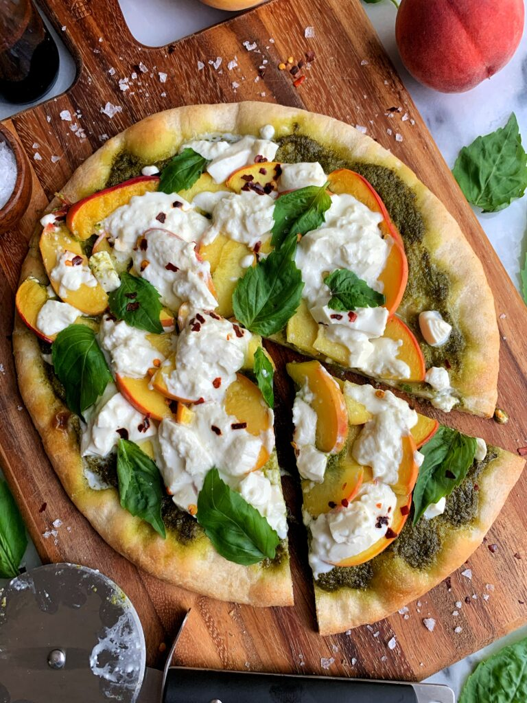 This Peach and Burrata Pizza with Balsamic Glaze is the ultimate peach flatbread recipe. Topped with pesto, peaches, burrata, fresh basil and a homemade balsamic glaze on top.
