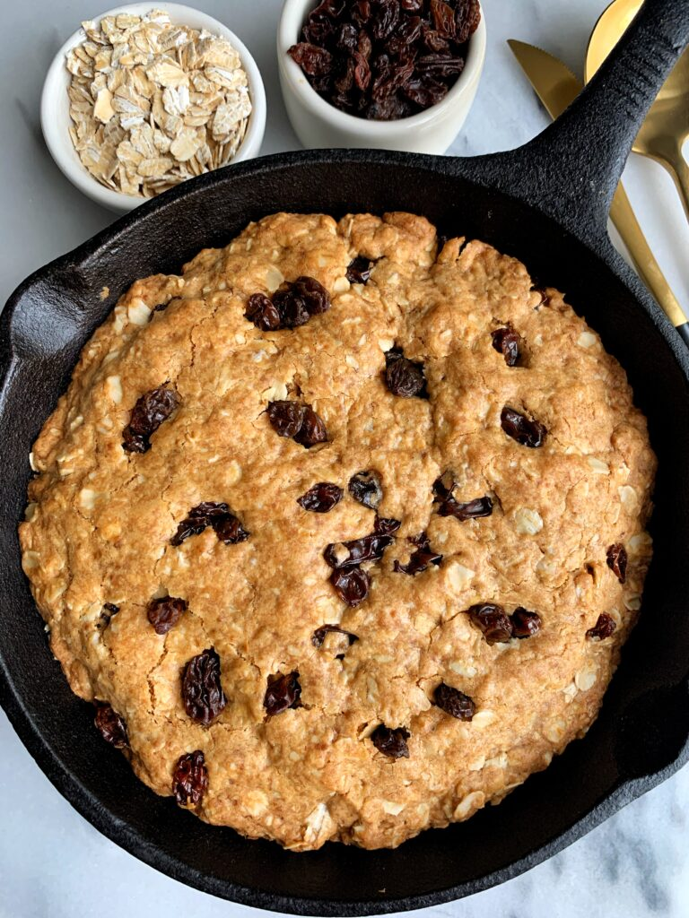 Deep Dish Oatmeal Raisin Cookie Skillet made with all gluten-free, dairy-free and nut-free ingredients! This is the ultimate healthier giant oatmeal cookie that tastes killer with your favorite ice cream on top.