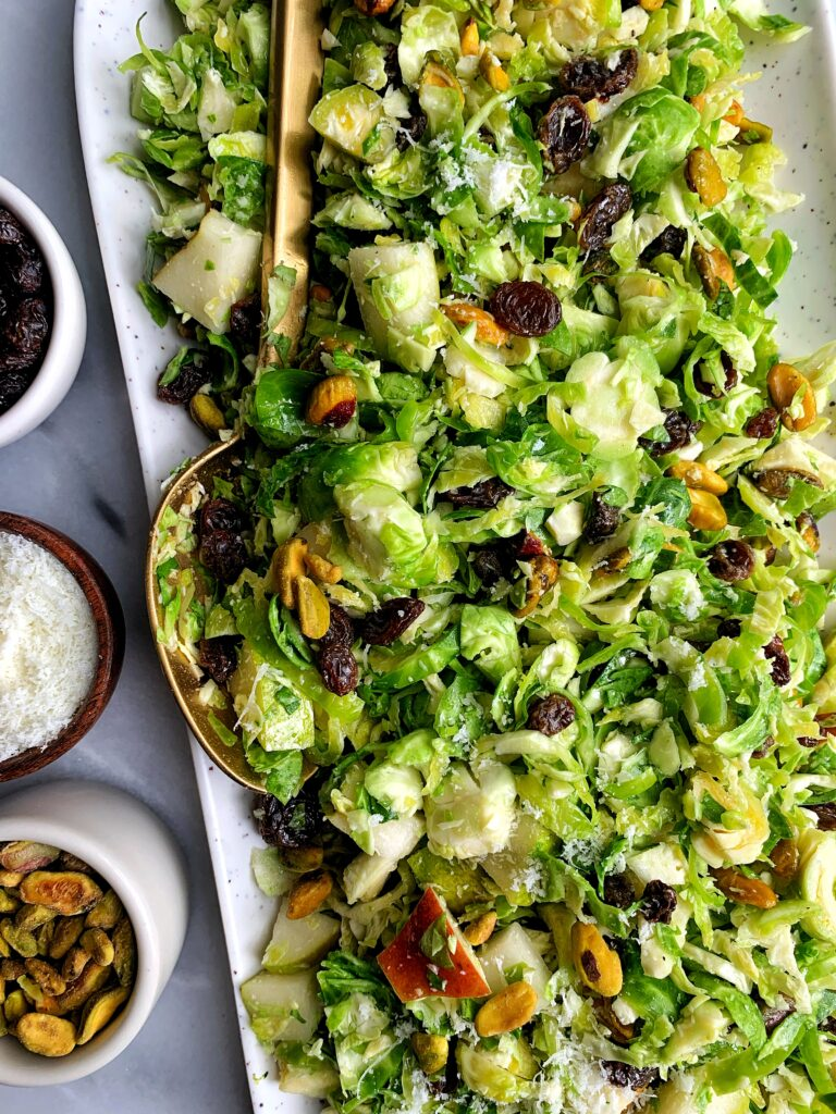 Crowd Pleaser Brussels Sprout Slaw! Made with raisins, pistachios, pears, pecorino and a simple dressing for an easy fall inspired salad.